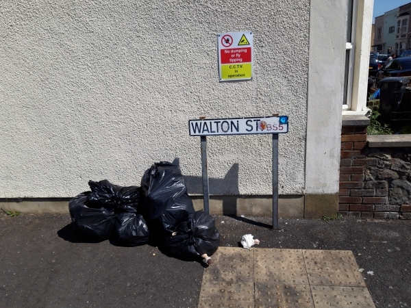 Photo shows fly-tipping beneath sign advising no fly-tipping, CCTV in operation