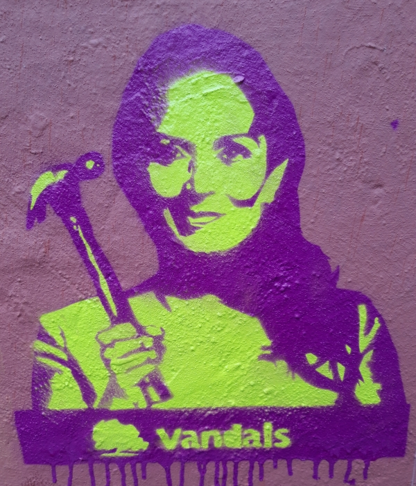 stencil art of Priti Patel holding hammer with the word vandals and the Conservative Party oak tree logo beneath