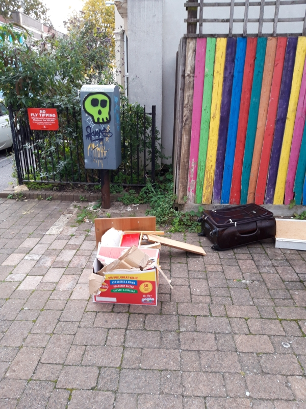 Cardboard and other items in front of no fly-tipping sign